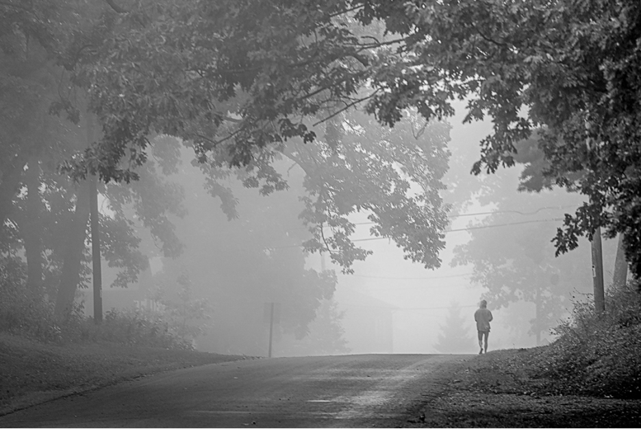 Black and white image of a person walking down a road.
